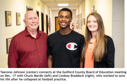 Taevone Johnson (center) connects at the Guilford County Board of Education meeting on Dec. 17 with Chuck Mardis (left) and Lindsey Braddock (right), who worked to save his life after he collapsed at football practice.