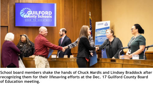 School board members shake the hands of Chuck Mardis and Lindsey Braddock after recognizing them for their lifesaving efforts at the Dec. 17 Guilford County Board of Education meeting.