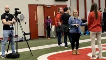 Representatives of the National Athletic Trainers' Association film an interview with Lindsey Braddock (in orange shirt, back to camera) about her efforts to save Taevone Johnson's life.